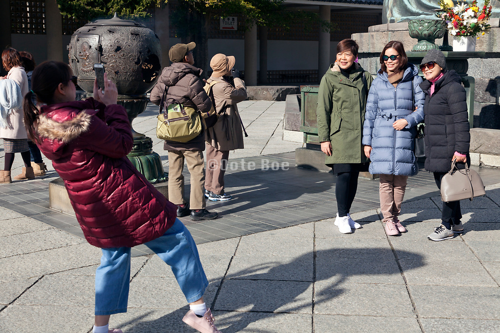 friends making photo in front of the big Buddha in Kamakura Japan