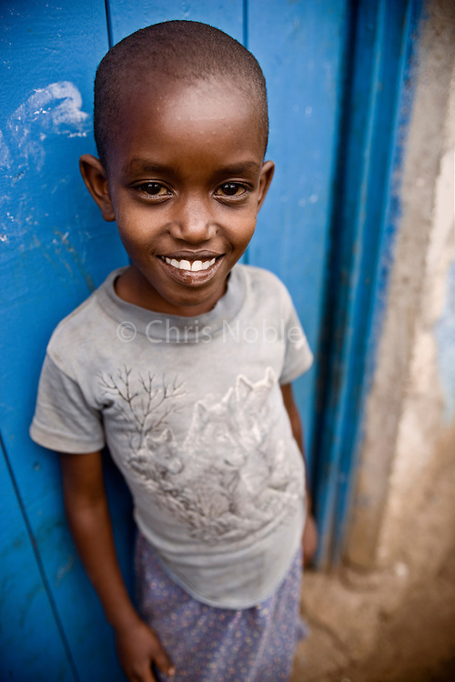 A  young girl stands before the blue door of her home in the genocide survivors village of Rugerero Rwanda.