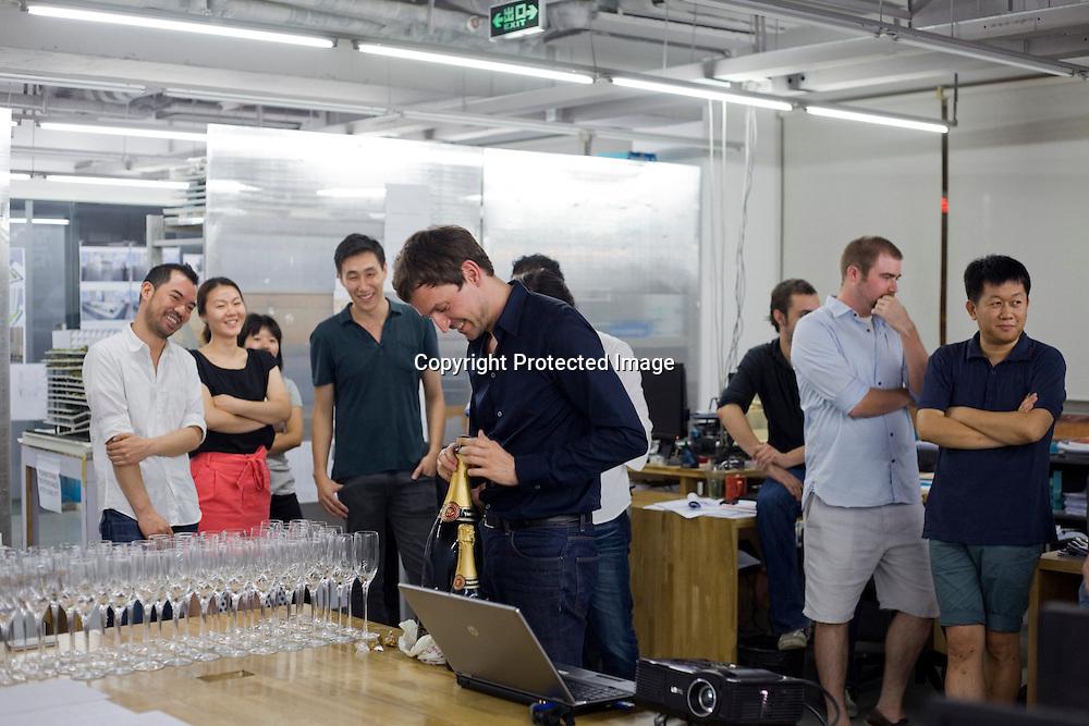 BEIJING, AUG.3, 2012 : Stararchitekt Ole Scheeren spendiert  seinen Mitarbeitern  Champagner , nachdem er  die neuesten Projekte in einer Slideshow im Ole Sceeren Buero vorgestellt hat.