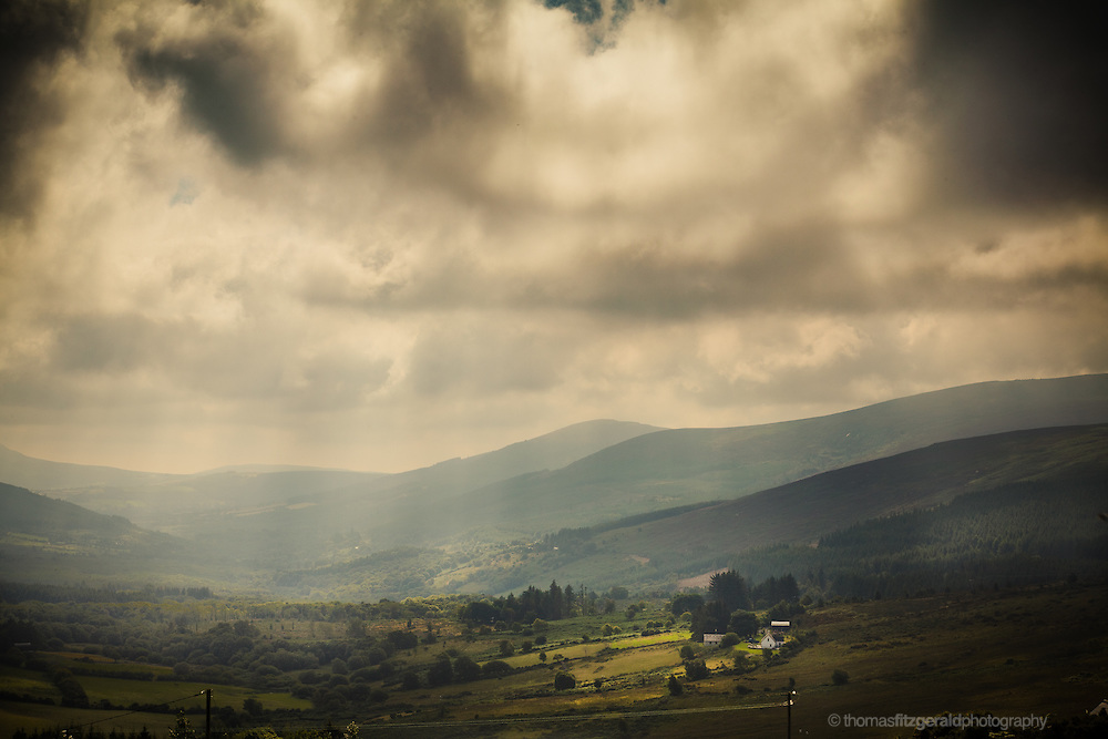 A Bank of rolling clouds hovers over a disant valley high in the picteresque mountains of Co. Wicklow valley high in the picteresque mountains of Co. Wicklow as the beams of light from the sun highlight a small farm house in the foreground