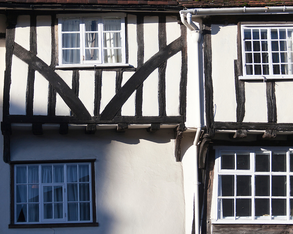 Detail of a timber framed facade with arch bracing, with a jetty supported by curved brackets at Lavenham, Suffolk, UK. 15th to 16th century