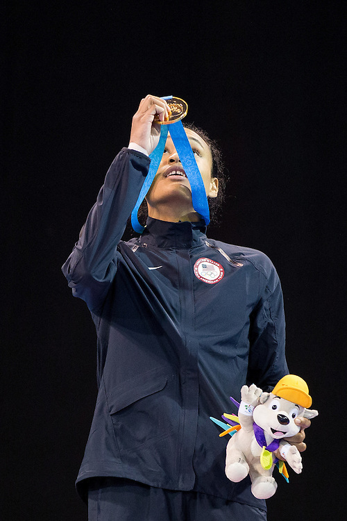 Gold medalist  Paige McPherson of the United States lifts her medal to the heavens during the medal ceremony for the women's taekwondo -67 kg division at the 2015 Pan American Games in Toronto, Canada, July 21,  2015.  AFP PHOTO/GEOFF ROBINS