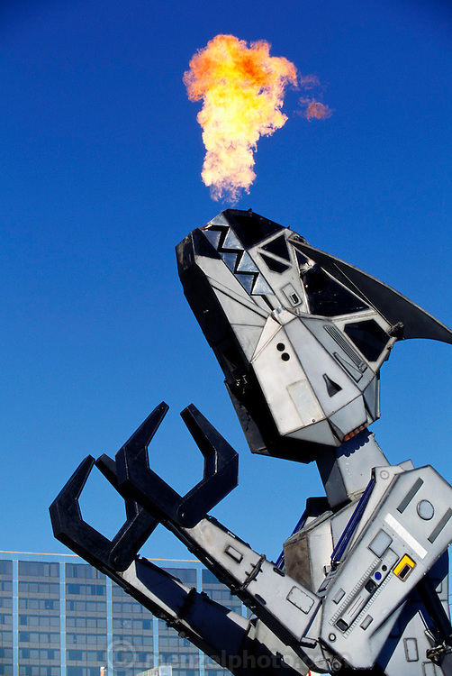Flames shoot from the jaws of Robosaurus, the human-piloted car-crushing entertainment robot. Robosaurus stands 12 meters high, weighs 26 tons and its jaws have a crushing force of nine tons. It uses this force to crush and tear cars to bits. American inventor Doug Malewicki created Robosaurus, demoed here in a parking lot behind a Las Vegas, Nevada casino. Nevada, USA