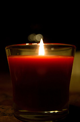 03 January 2015:   red candle in a clear glass container burning on a marbled table top