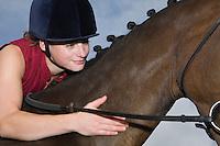 Girl hugging horse close-up