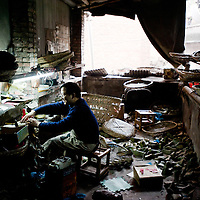 Chongqing, China - 31 December 2010:  a man works in a messy shoe factory. According to a report published by Bank of America Merrill Lynch's David Cui, titled 'Not So Trivial Facts', China has produced in 2010 a total of 12.6 billion pairs of shoes which means 9.4 pairs of shoes per person, compared with 1.3 pairs in the rest of the world (63.0 percent of global total).