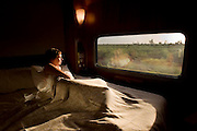 The Ghan.  Passenger Rebecca Barnes waking up early to watch the sunrise from the comfort of her Platinum Serive cabin, over the desert approximately 200kms south of Tennant Creek and 300kms north of Alice Springs. Image © Arsineh Houspian/Falcon Photo Agency.