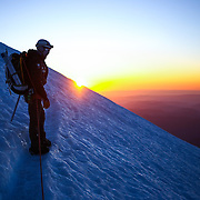 A climber ascends the mountain as the sun rises during a summit of Mount Rainier on June 30, 2015. The iconic Pacific Northwest volcano is a popular challenge for mountaineers.  (Joshua Trujillo, seattlepi.com)