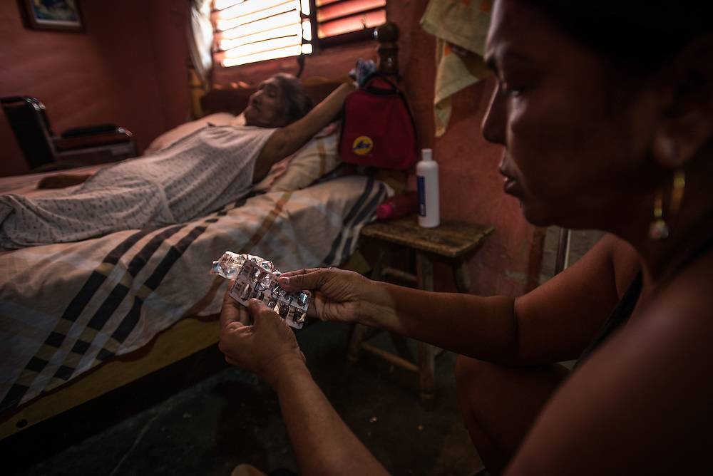 "LA VELA, VENEZUELA - SEPTEMBER 11, 2016: Maria Piñero talks with her sister about how their mother's pills are running out again, while they take care of their mother, Felipa Palencia de Piñero, who is diabetic. The family struggles to find the medicine that she needs. To escape the crisis, Ms. Piñero spent all of her savings to pay smugglers to take her in a small fishing boat to Curacao island. ""I'm nervous,"" she said. ""I'm leaving with nothing. But I have to do this. Otherwise, we will just die here hungry."" Another benefit of living and working in Curacao, she said, is that she will be able to find and pay for her mother's medicines, and ship them to her in Venezuela.  Despite having the largest known oil reserves in the world, Venezuela is suffering from hyperinflation and a severe economic crisis making affordable food difficult for most middle and working class families to access.  Well over 150,000 Venezuelans have fled the country in the last year alone, the highest in more than a decade, according to scholars studying the exodus. As Hugo Chávez's Socialist-inspired revolution collapses into economic ruin, as food and medicine slip further out of reach, the new migrants include the same impoverished people that Venezuela's policies were supposed to help. ""We have seen a great acceleration,"" said Tomás Paez, a professor who studies immigration at the Central University of Venezuela. He says that as many as 200,000 Venezuelans have left in the last year, driven by how much harder it is to get food, work and medicine — not to mention the crime such scarcities have fueled.  PHOTO: Meridith Kohut for The New York Times"