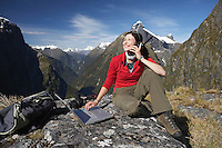Woman using walkie-talkie and laptop on mountain peak