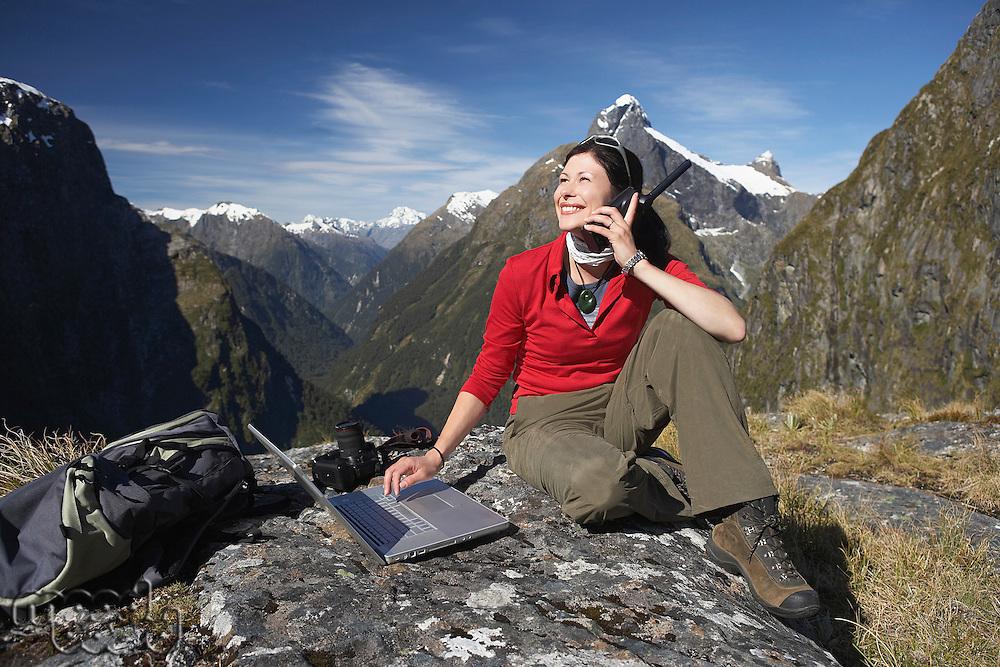 Woman using walkie-talkie and laptop on mountain peak