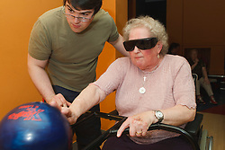 Volunteer with visually-impaired wheelchair user at ten pin bowling alley.