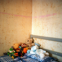The bare walls in 2 much loved childrens bedroom in South London. Their mother is hoping to get a grant to fix the room up. She is alone with three chidren, her boyfriend is in jail.