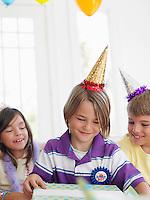 Three children (7-12) at birthday party one boy opening present