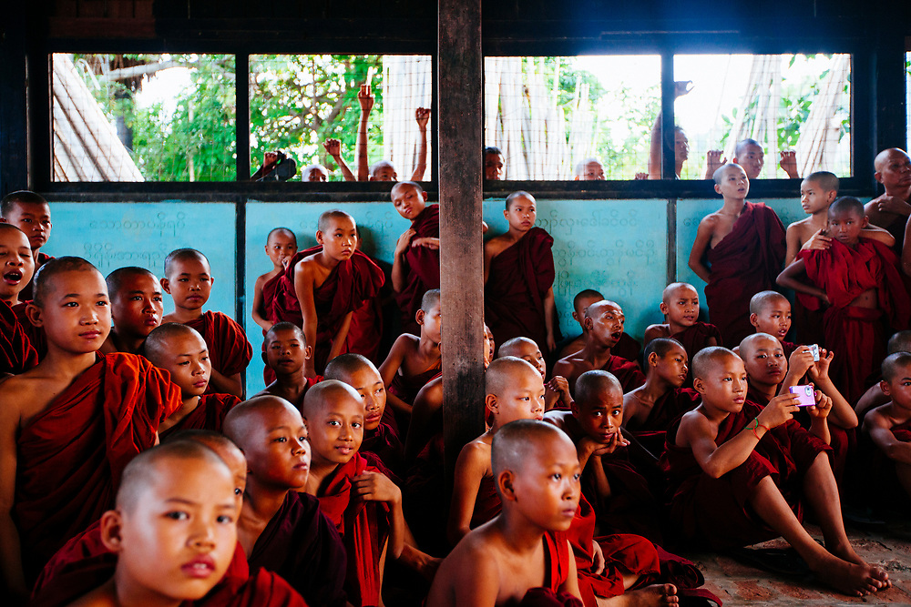 A group of novice monks watch a performance in Mandalay, Myanmar.