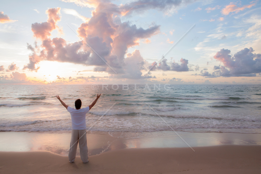 man standing by the ocean with raised arms as the sun rises above the ocean in Fort Lauderdale, FL
