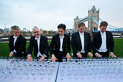© licensed to London News Pictures. London, UK 06/01/2014. The Royal Philharmonic Orchestra performs a concert played entirely through hundreds of glasses of water to benefit WaterAid at Potter's Field Park in London on Monday, 6 January 2014. The concert, which took 174 hours to prepare, features performances of songs by Katy Perry, One Direction, Adele, Gary Barlow and Taylor Swift. Photo credit: Tolga Akmen/LNP