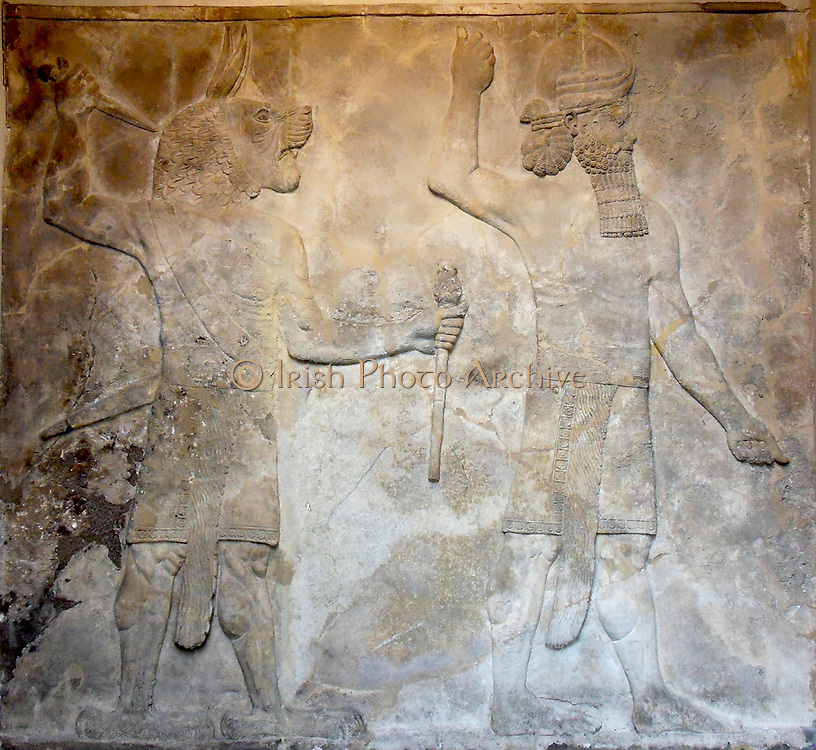 Stone relief from the South-West Palace of King Sennacherib (reigned 704-681 BC), Nineveh, northern Iraq. Neo-Assyrian, 704-681 BC. On the right stands an empty-handed man wearing the horned headdress of a god. This may be the god 'House God', associated with frightening away the effects of witchcraft. The lion-headed, eagle-footed man holding a mace and upraised dagger is an ugallu (great lion or great storm demon).