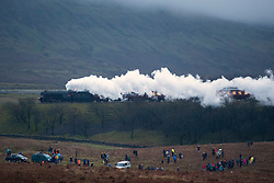 © Licensed to London News Pictures. 06/02/2016. Ribblehead UK. The iconic steam train the Flying Scotsman 60103, the first Locomotive to reach 100mph in 1934 has made it's first main line test today hauling the Cumbrian Mountain Express from Carnforth to Carlise after a £4.2m restoration. Pictured this evening crossing the Ribblehead Viaduct. Photo credit: Andrew McCaren/LNP