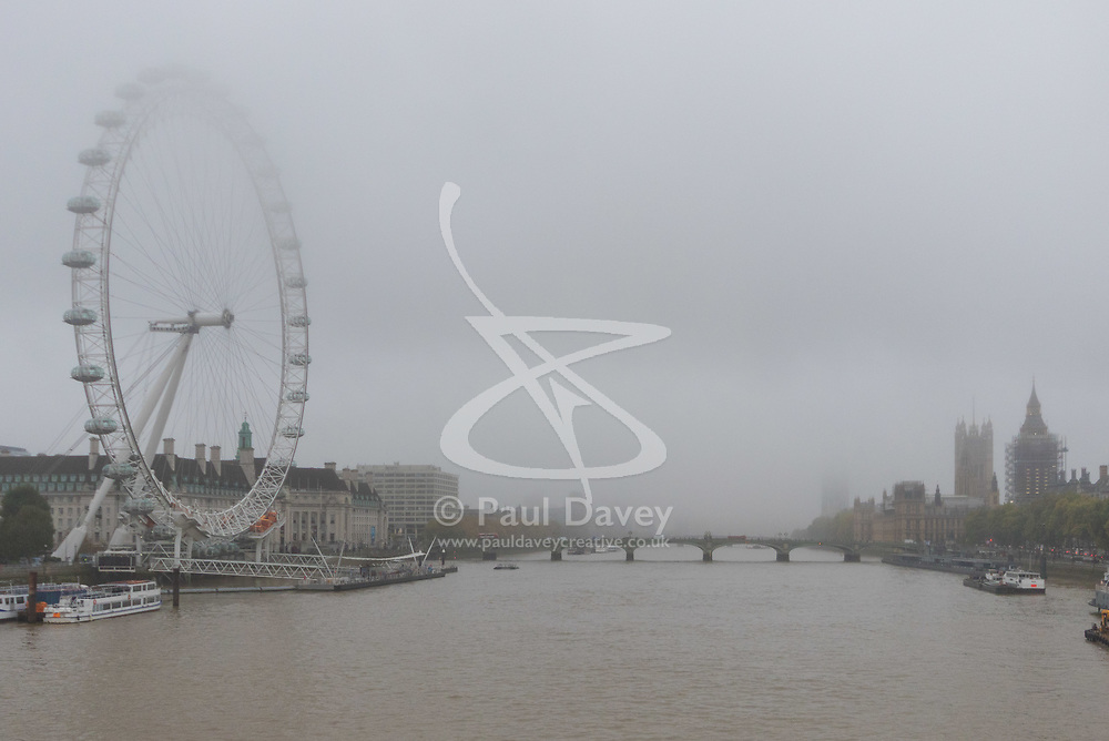 London, October 26 2017. The top of the London eye and the Houses of Parliament beyond are partially obscured by fog as London wakes up to a cool, misty autumn morning. © Paul Davey