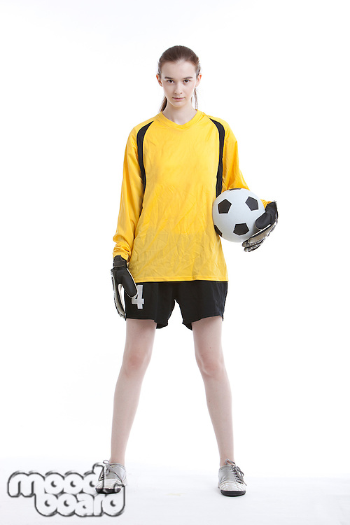 Portrait of young woman with soccer ball against white background
