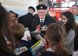 © Licensed to London News Pictures. 29/05/2014.   David Roberts, a Royal Navy D Day veteran is crowded by school children who ask for his autograph in the Caen museum and Peace Garden in Normandy.   Photo credit : Alison Baskerville/LNP