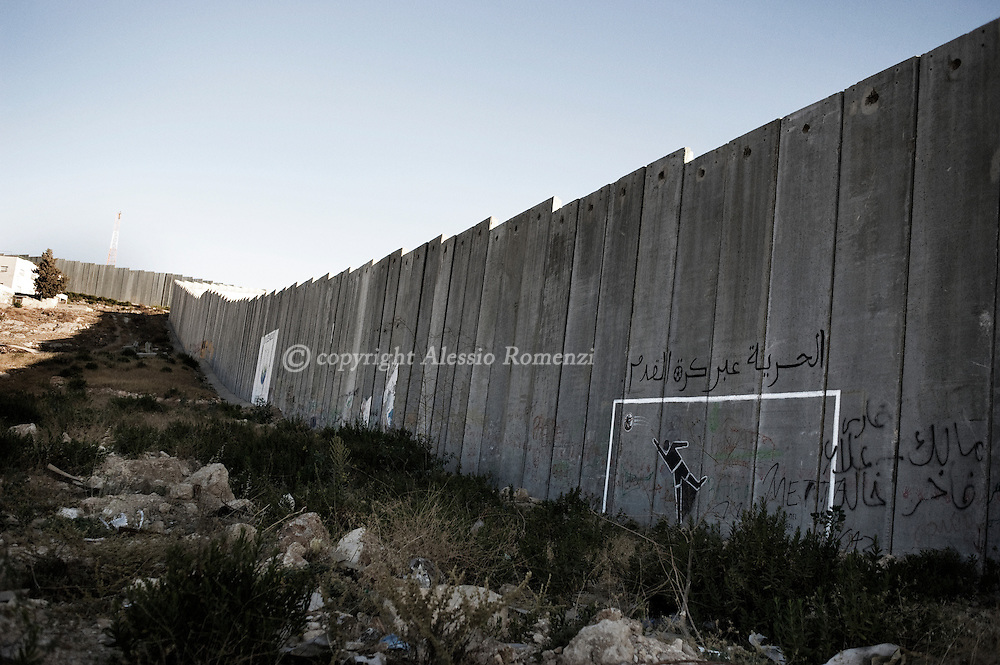 Grafitti showing a goal post with a goalie reaching for a football and the words 'Freedom is through football' is seen painted on a section of the controversial Israeli separation barrier in the West Bank village of Abu Dis, on the outskirts of Jerusalem on June 8, 2010.© ALESSIO ROMENZI