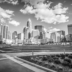 Charlotte skyline black and white image at Romare Bearden Park with downtown Charlotte city buildings against a cloudy sky. Includes One Wells Fargo Center, Two Wells Fargo Center, Bank of America Corporate Center, Bank of America Plaza, 121 West Trade building, and Carillon Tower. Charlotte, North Carolina is a major city in the Eastern United States of America