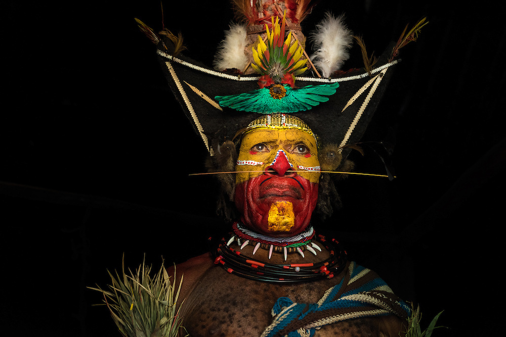 Fully decorated Huli wigmen sits in his hut and shows his wig made of human hair and decorated with feathers of Bird of Pasadise, Tari, Papoea new Guinea.