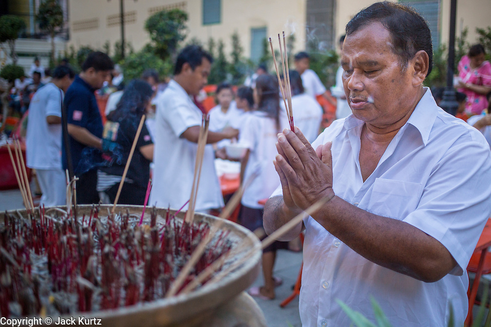 27 JANUARY 2013 - BANGKOK, THAILAND: A man prays during Thaipusam at Dhevasathan (the Brahmin Shrines) on Dinso Rd in Bangkok. Thaipusam is a Hindu festival celebrated primarily by the Tamil community in South East Asia on the full moon in the Tamil month of Thai (Jan/Feb). Pusam refers to a star that is at its highest point during the festival. The festival commemorates both the birthday of the Hindu god Murugan, son of Shiva and Parvati, and the occasion when Parvati gave Murugan a vel (a lance) so he could vanquish the evil demon Soorapadman. The holy day is celebrated by Brahmins in Thailand. Brahmanism was the court religion before Buddhism came to Thailand and before the foundation of Sukhothai. Both religions are combined in the Thai way of life and its customs and ceremonies.        PHOTO BY JACK KURTZ