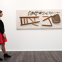 London, UK - 15 October 2014: a gallery assistant looks at 'Cadira trencada, 1993' by Antoni Tàpies during the first day of Frieze Art Fair and Frieze Masters in Regent's Park.