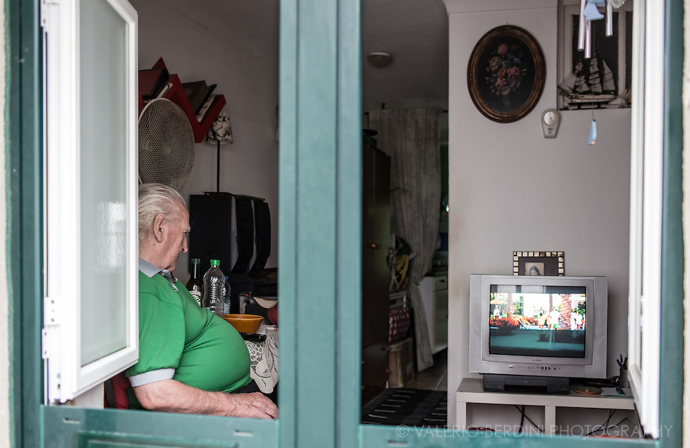 A man watches the television in his living room, window door opens on the street.