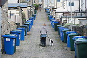 A woman pushes a pram while walking a dog on a lead, up  a cobbled back street lined with wheelie bins,  in Skipton, North Yorkshire, UK.