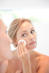 Woman Using  Cleansing Cotton Pad on Face
