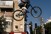 Israel, Tel Aviv, Bicycle stunt at an urban street party in Dizengoff street