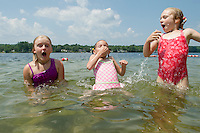Lauren MacDonald, Evelyn Smith and Sage Paterson take a dunk to cool off at Bond Beach as temperatures rise Wednesday afternoon.  (Karen Bobotas/for the Laconia Daily Sun)