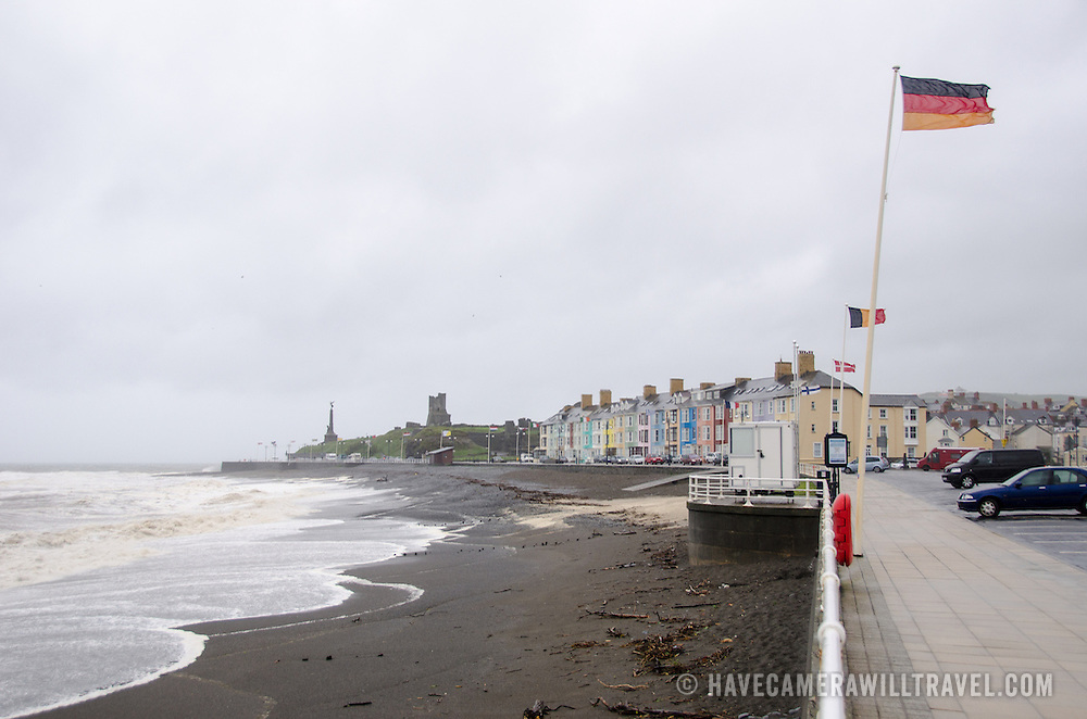 A storm hits the beach in Aberystwyth on the western coast of Wales. In the distance in center of frame are the remains of the castle.