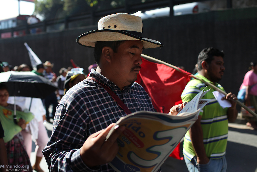 Daniel Pascual, director of the Committee for Campesino Unity (CUC), marches while reading a newspaper. After 9 days and 212 kilometers, the Indigenous, Campesino and Popular March for the defense of Mother Earth, against evictions, criminalization, and in favor of Integrated Rural Development, arrived to the Capital City. According to members of the CUC, it is estimated that about 15,000 people participated in the ninth and final day of the march.