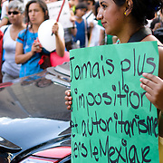 """Young woman holds a sign saying """"No more authoritarinism against Mexico and democracy"""" during a protest in Montreal after Enrique Pena Nieto got elected as the new mexican president."""
