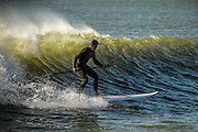 Chris Blackway and others surf at the end of Long Beach Island near the town of Beach Haven, NJ.