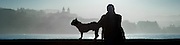 Silhouette of man and his dog sat on balaustrade in San Sebastian (Spain)