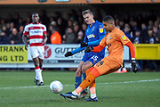Doncaster Rovers goalkeeper Seny Dieng (24) clearing from AFC Wimbledon attacker Marcus Forss (15) during the EFL Sky Bet League 1 match between AFC Wimbledon and Doncaster Rovers at the Cherry Red Records Stadium, Kingston, England on 14 December 2019.
