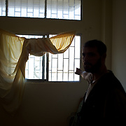 Mostafa Haloum, a syrian army defector, points in the direction of his hometown through the window of an improvised room at a refugee center in Wadi Khaled, northern Lebanon.