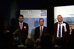 UKIP leader Nigel Farage (centre) tries to contain his emotions during Conservative candidate Craig MacKinlay's victory speech after the announcement of the 2015 South Thanet election results in the Winter Gardens, Margate. Pictured to his right is Al Murray who gained 318 votes and to his left Will Scobie, the Labour party candidate who gained 11,700 votes. Photo credit: Mary Turner