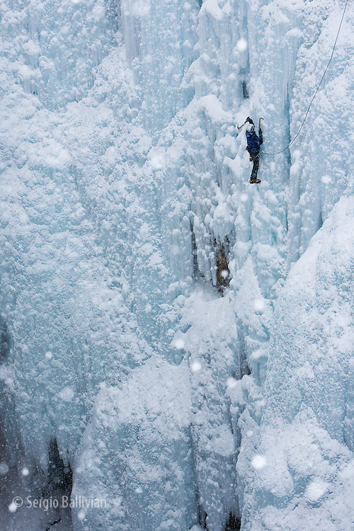 Ice climbers in the Ouray Ice Park scale vertical curtains of ice in the middle of a winter storm in The San Juan mountains in Ouray, Colorado.