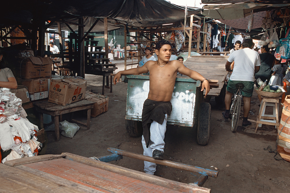 A young man rests against his cart in a public market in León, Nicaragua.