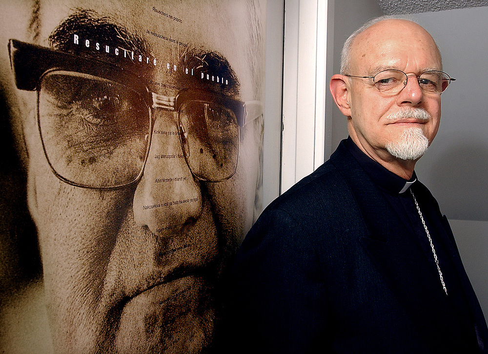 Cit12/13/02  Photo by Mara Lavitt-Rosazza<br /> ML0041B #3650<br /> Bishop Peter Rosazza in his Sherman Ave. residence and offices.  At left is a poster of Archbishop Oscar Romero who was murdered in El Salvador in 1980 because of Romero's activism on behalf of the poor.