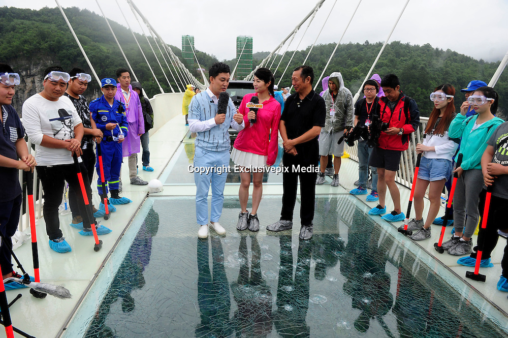 ZHANGJIAJIE, CHINA - JUNE 25:<br /> <br /> A radio broadcast is taken on glass-bottomed bridge for a safety test at Zhangjiajie Grand Canyon on June 25, 2016 in Zhangjiajie, Hunan Province of China. World\'s tallest and longest glass-bottomed bridge has been completed and took a global broadcast through television and internet medias to show its safety. More than thirty citizens and visitors thumped the bridge with hammer in the test event. <br /> &copy;Exclusivepix Media