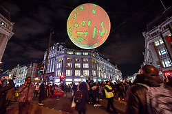 "© Licensed to London News Pictures. 19/01/2018. LONDON, UK.  ""Origin of the World Bubble"" by Miguel Chevalier, a giant balloon, suspended above Oxford Circus, is illuminated for the first time.  Lumiere London, the capital's largest arts festival commissioned by The Mayor of London and produced by Artichoke.  Light installations by leading artists have been set up, both north and south of the river for the public to view 18-21 January.  Photo credit: Stephen Chung/LNP"