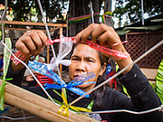 07 SEPTEMBER 2016 - BANGKOK, THAILAND:  A woman ties ribbons a on a sculpture meant to represent the heart of the Pom Mahakan community during a community meeting Wednesday. Forty-four families still live in the Pom Mahakan Fort community. The city of Bangkok has given them provisional permission to stay, but city officials say the permission could be rescinded and the city go ahead with the evictions. The residents of the historic fort have barricaded most of the gates into the fort and are joined every day by community activists from around Bangkok who support their efforts to stay.      PHOTO BY JACK KURTZ